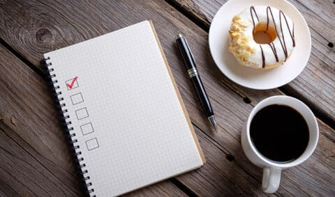 Photo of notebook on a table with a coffee and donut