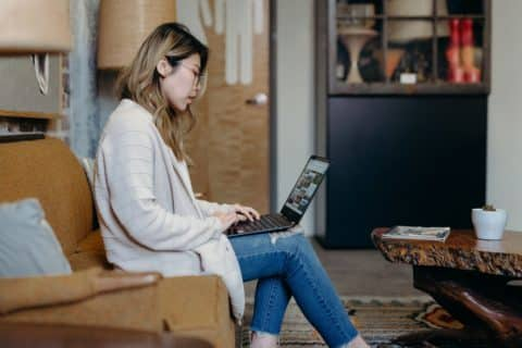 woman in jeans sitting on a couch with a laptop
